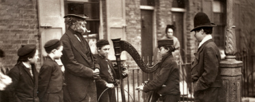 Italian child playing a harp to a small crowd